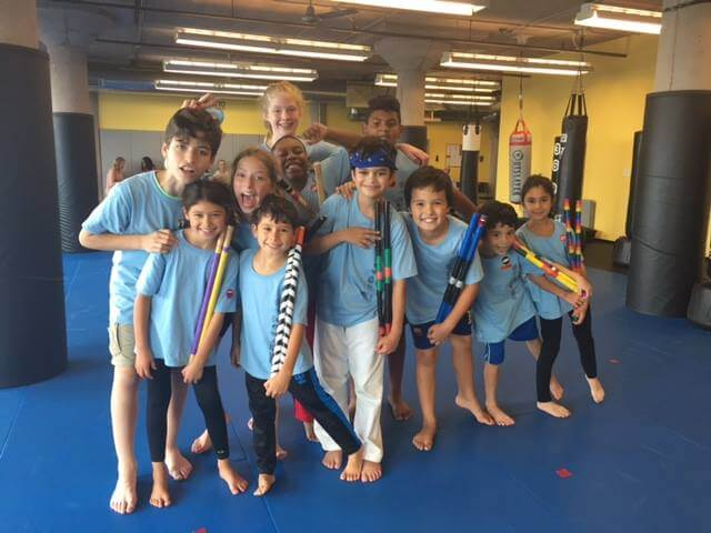 kids holding Kali Sticks in a martial arts gym
