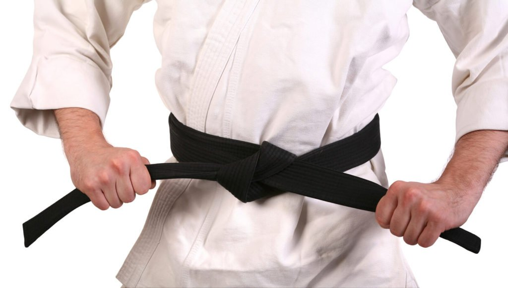 a martial arts student tying a black belt