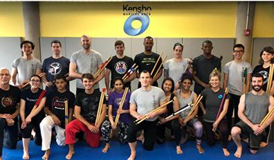 martial arts students holding kali sticks