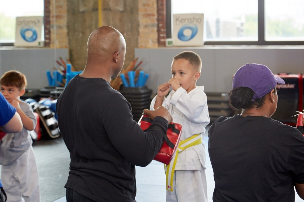 father and son practicing martial arts in class