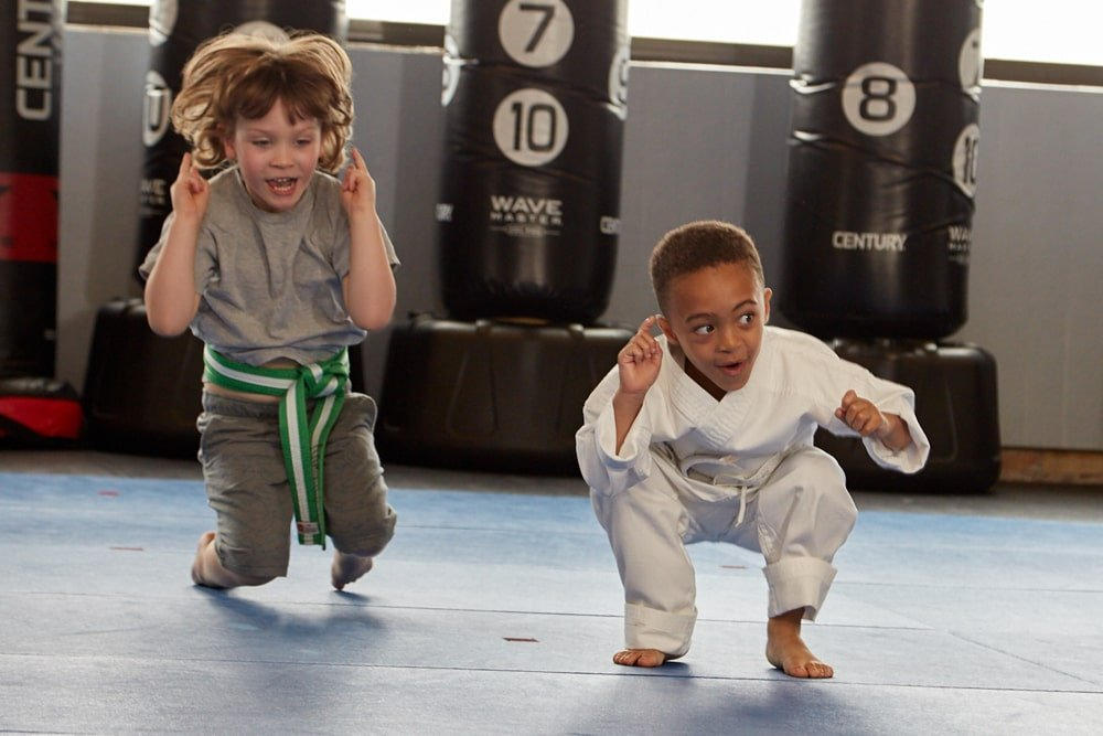 kids jumping on the mat in karate class