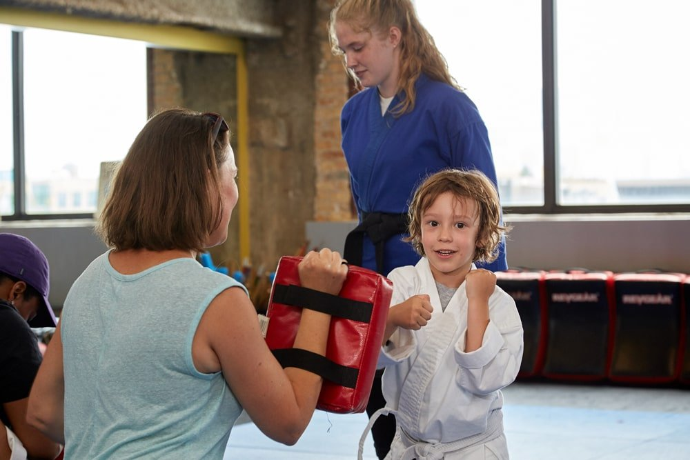 mother and child practicing martial in the dojo